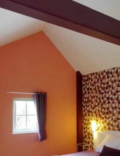 Vue sur une chambre avec un papier peint géométrique prune et rose corail en tête de lit © francois louchet, par CREA DECO, Décoratrice UFDI à Honfleur, Deauville, Caen - 14